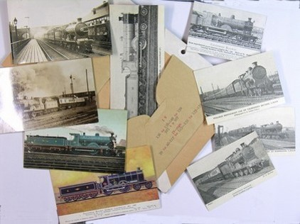 Nine postcards and photographs with images of trains laid out around the envelope that contained them, ready to be catalogued by the volunteers