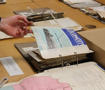 A binder from the collection full of railway ephemera with a person's hand turning a page showing a magazine with the title Locomotive