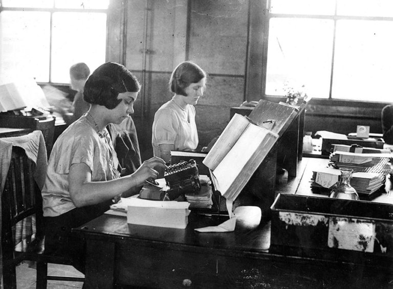Civil Service publicity: photographs showing different activities undertaken at the census office in Acton, London, including punching of machine cards and stacking and filing schedules for the 1931 census; also pictured is the battery of Powers-Samas printing/counting/sorting machines.