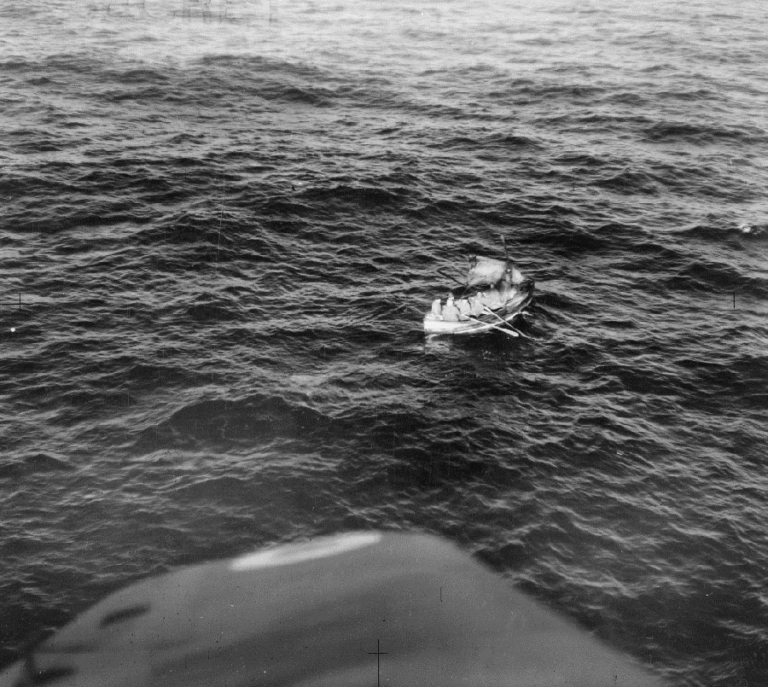 Black and white photograph of troops adrift aboard a rowboat with sail during Dunkirk Evacuation, June 1940.