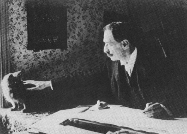 Black and white photograph of Louis Wain at his drawing table in 1890.