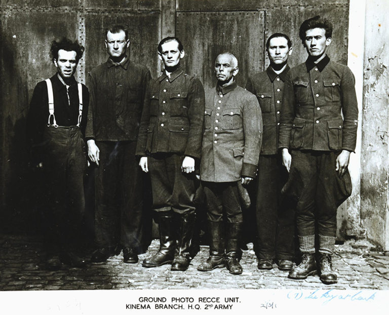 A British 2nd Army reconnaissance unit photograph of six of the 45 defendants of the Bergen-Belsen Trial in May/June 1945. These men, who had served as SS camp guards at the Bergen-Belsen Transit Camp and Auschwitz Concentration Camp, include an Unterscharführer named Joachim Wolf (third man standing from left) who assisted in the murder of Able Seaman Keith Mayor.