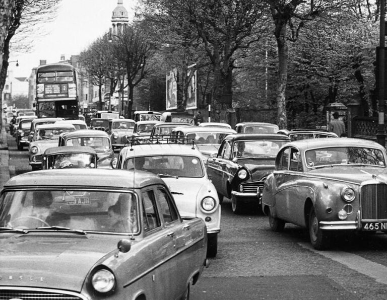 A black and white photograph of traffic congestion in central London, featuring numerous cars and a bus.