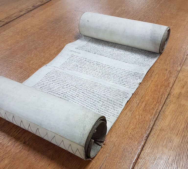A medieval parliament roll displayed on a table.