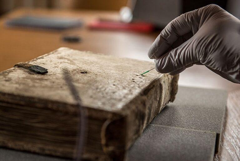 Researchers from BioArCh non-destructively sampling the Gospels of Luke cover.