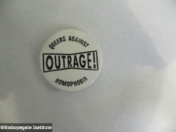 A pin badge from 'Outrage! Queers Against Homophobia' from 1990.
