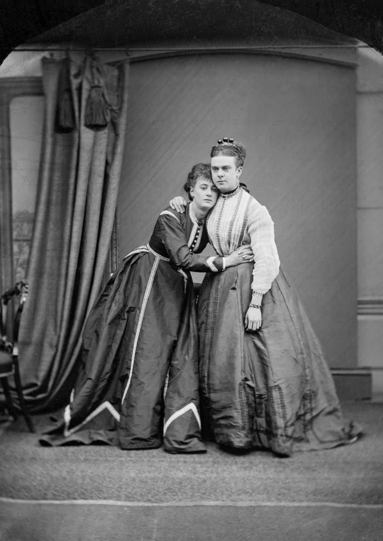 Black and white portrait photograph of Fanny and Stella taken in 1869. They are standing together holding on to one another.