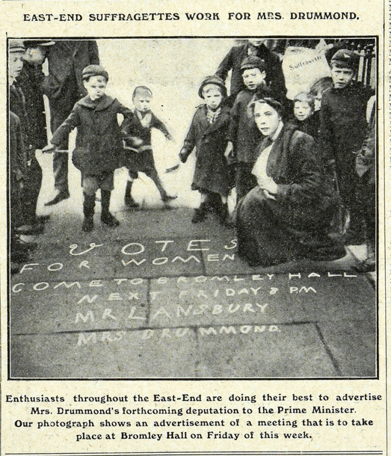 A black and white photograph showing a woman surrounded by children. On the paving stones in front of her is written 'Votes for Women come to Bromley Hall next Friday 8pm.' The headline on the page reads 'East-End Suffragettes work for Mrs Drummond'. The caption below reads 'Enthusiasts throughout the East-End are doing their best to advertise Mrs Drummond's forthcoming deputation to the Prime Minister. Our photograph shows an advertisement of a meeting that is to take place at Bromley Hall on Friday of this week'.