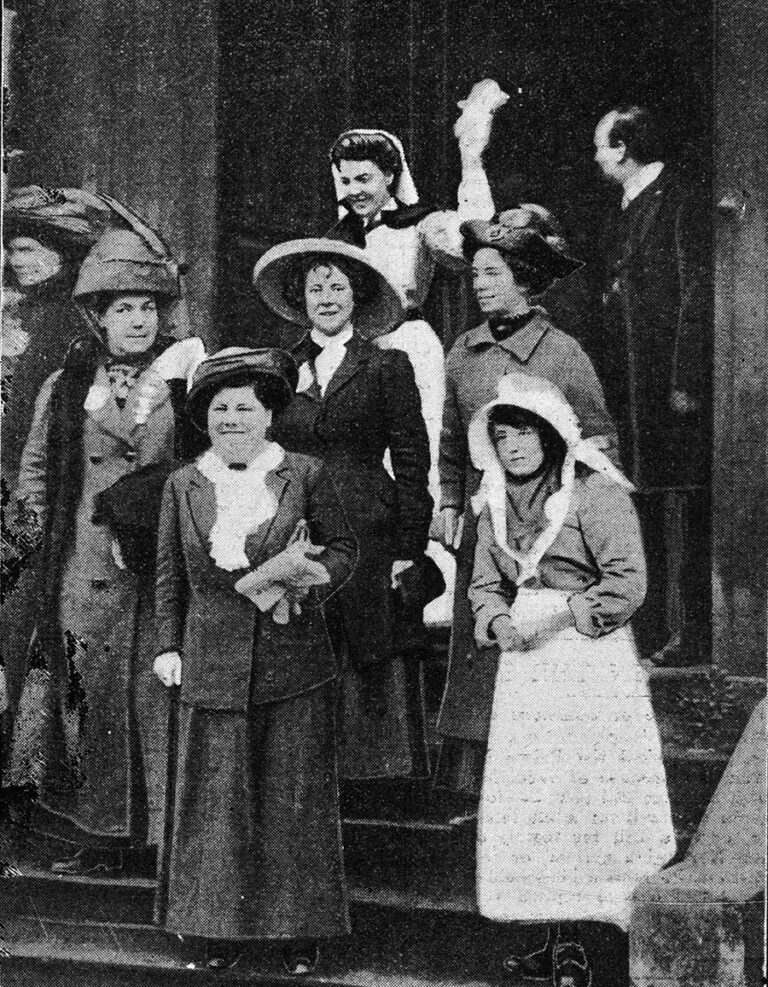 A group of seven suffragettes emerging from a building looking triumphant.