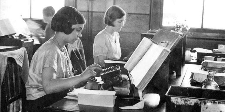 Publicity photograph showing punching of machine cards for the 1931 census at the Census Office in Acton. The photograph shows two young women at work in the office.
