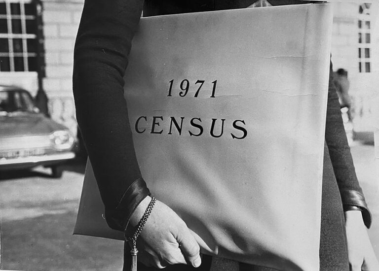 A photograph of someone carrying a satchel with the wording 1971 census.