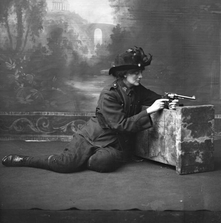 Studio portrait of Constance Markievicz in uniform with a revolver.