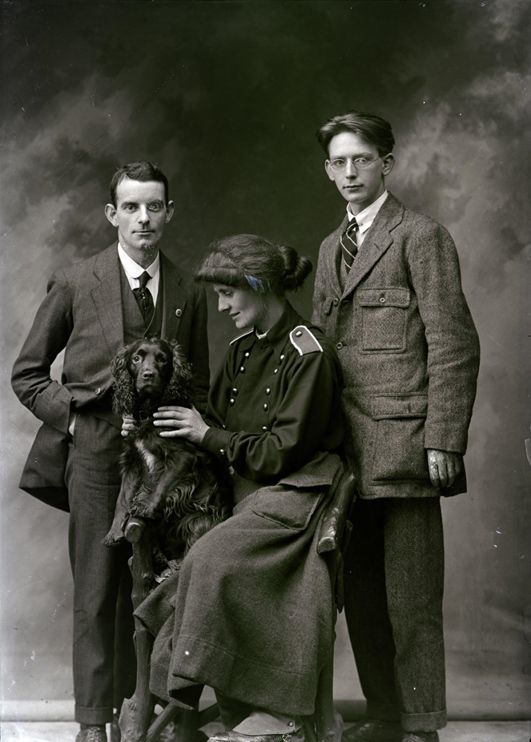 A posed photograph with The Countess surrounded by two senior Fianna officers as she holds her dog Poppet.