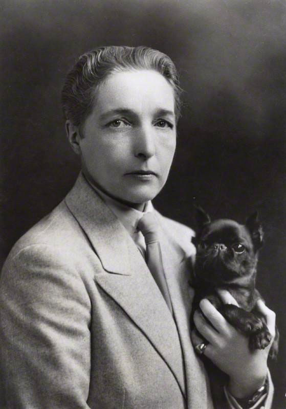 Black and white photograph of author Radclyffe Hall holding a small black dog.