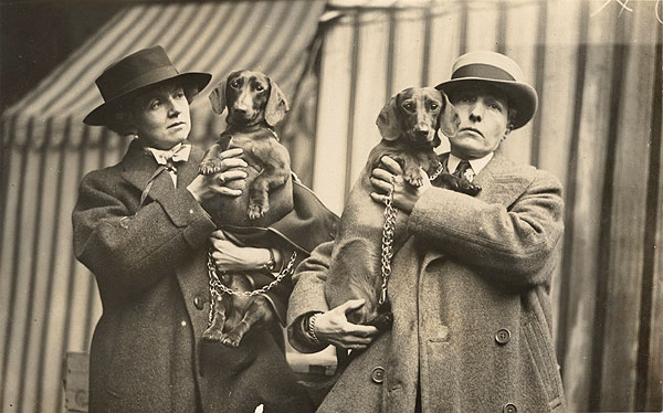 Black and white photograph of Una Troubridge and Radclyffe Hall holding their dogs in 1923. Both women are dressed in woollen overcoats and wide-brimmed hats.