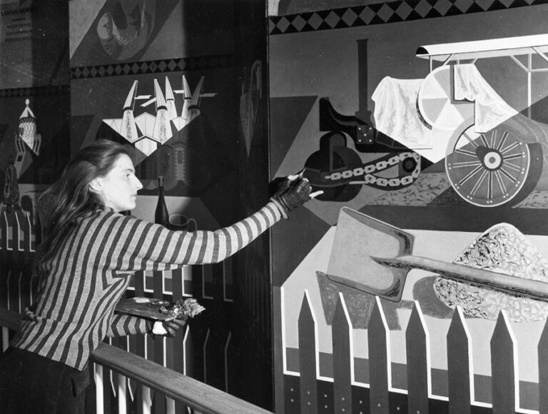 Photograph of Sheila Robinson working on the Edward Bawden Country Life Mural, Lion and Unicorn pavilion.
