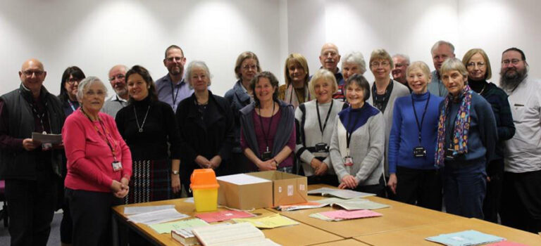 A group of volunteers, consisting of 20 men and women and staff from The National Archives, standing around a table upon which are spread out documents from the archives.