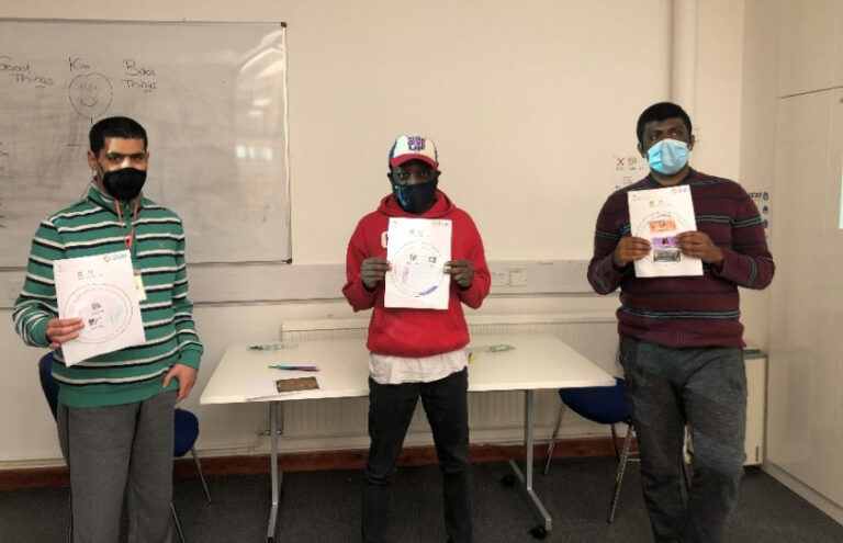 Three of the students from Share community holding up pictures of their completed seals.