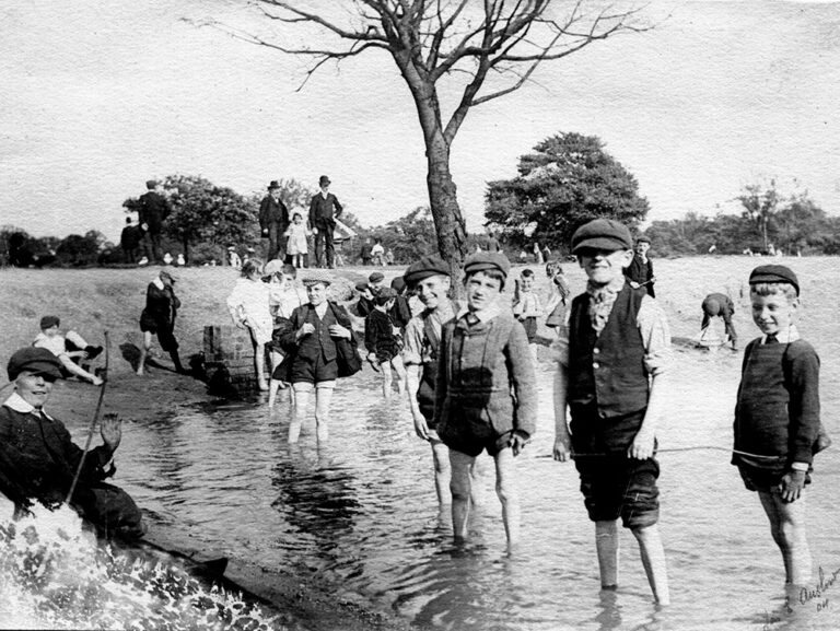 A black and white photograph of a group of boys wading in the pond on Tooting Common, London, taken in 1904.