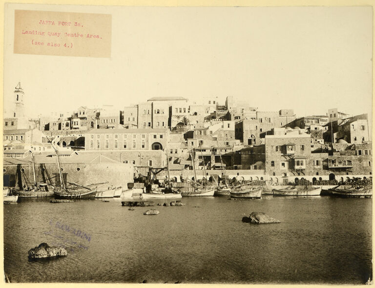 Sepia tinted photograph of Jaffa Port, Palestine, in the 1920s. The scene is a busy port with numerous ships and boats overlooked by the town's buildings. The British administration undertook the development of Jaffa as a modern port during the 1920s and 1930s.