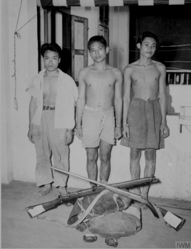 Three young Malayan men stand in front of pile of rifles.