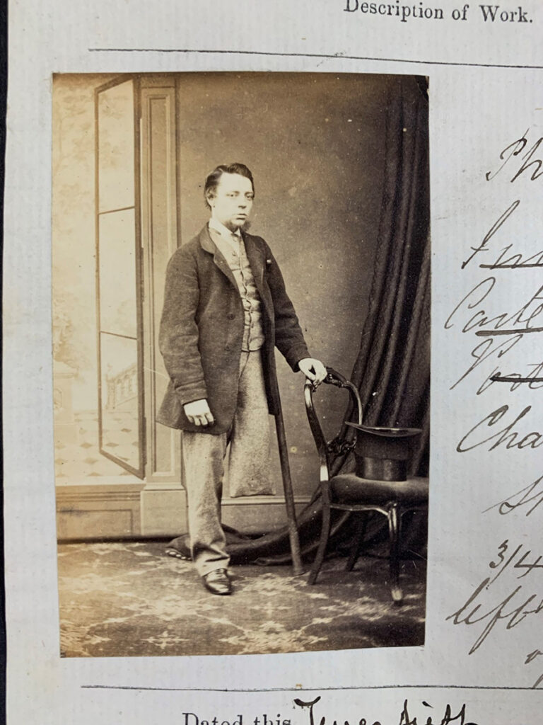Photograph of Charles Moore, standing, ¾ face, left hand on back of chair'.