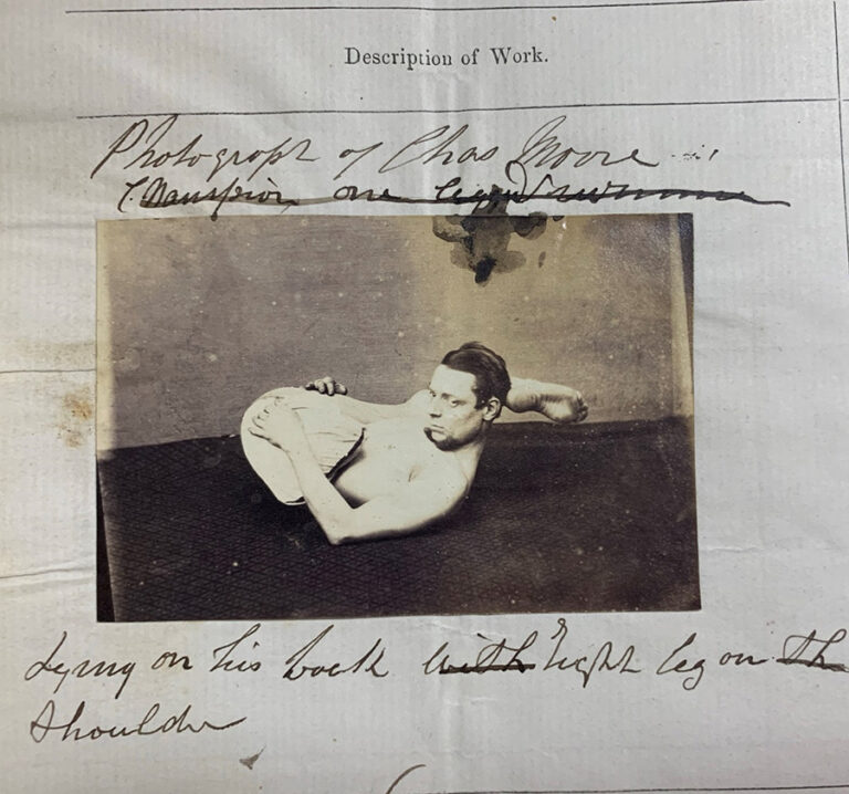Photograph of Charles Moore, lying on his back, right leg on shoulder.