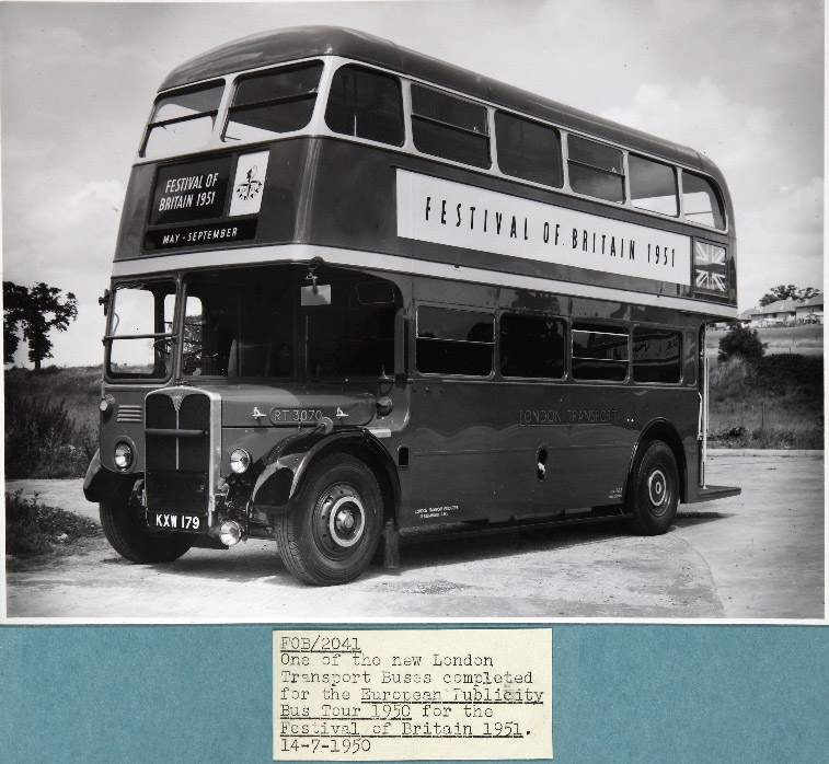 One of the Festival of Britain tour buses. On its side is a big poster advertising the Festival of Britain. The bus looks like a Routemaster bus.